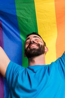 Homem sorridente contra a bandeira lgbt