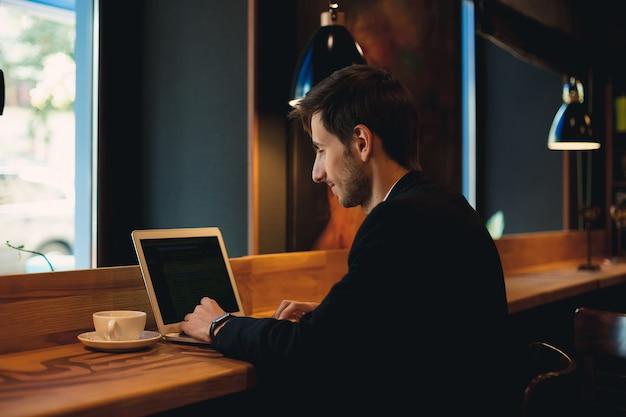Homem sorridente, conversando no laptop tomando café
