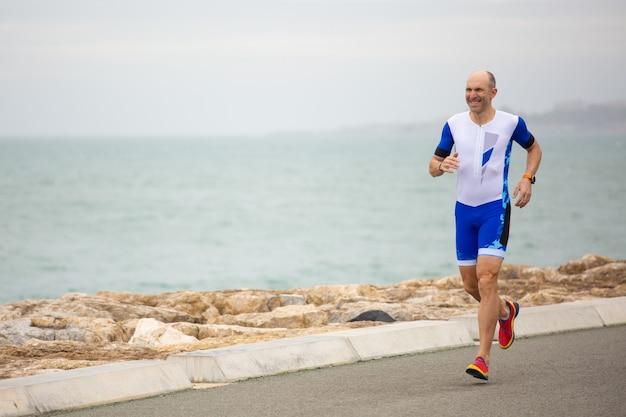 Homem sorridente correndo na costa do mar