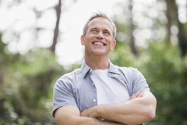 Homem sorridente, cruzando seus braços, exterior