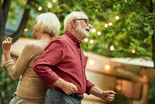Homem sorridente de cabelos grisalhos e óculos dançando com a esposa de costas um para o outro