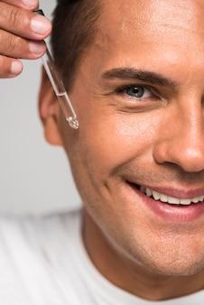 Homem sorridente de close-up aplicando soro