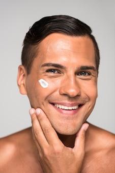 Homem sorridente de close-up com creme facial Foto gratuita