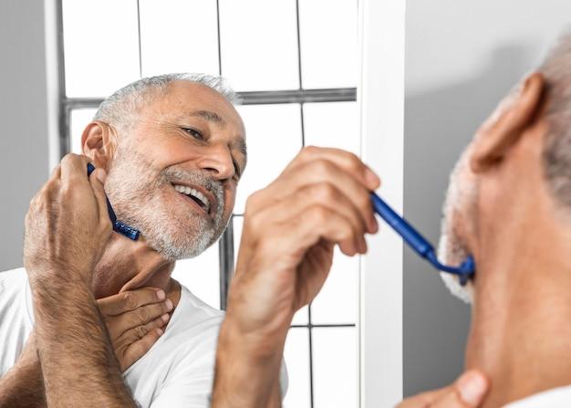 Homem sorridente de close-up se barbeando no espelho