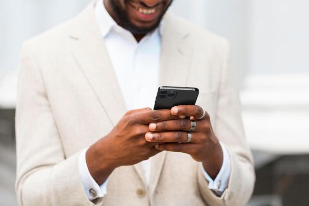 Homem sorridente de close-up segurando um smartphone