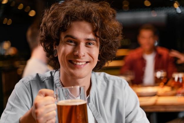 Homem sorridente de close-up segurando uma caneca de cerveja no bar