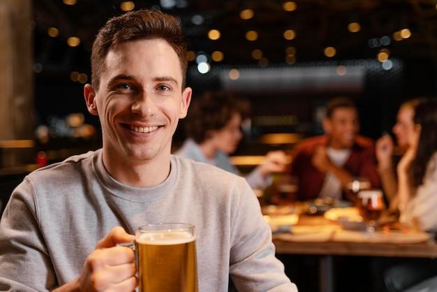 Homem sorridente de close-up segurando uma caneca de cerveja