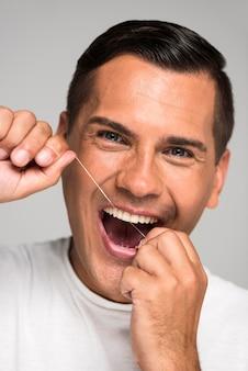 Homem sorridente de close-up usando fio dental