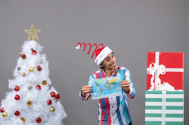 Homem sorridente de frente e chapéu de papai noel com mola espiral segurando um mapa do mundo