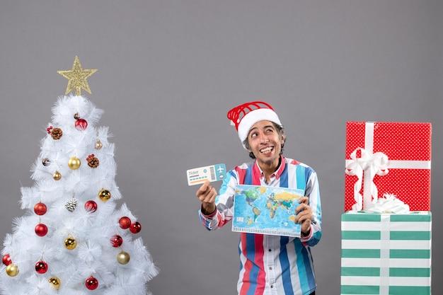 Homem sorridente de frente e olho piscando segurando mapa-múndi e bilhete de viagem