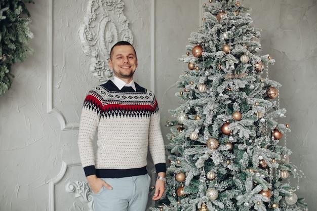 Homem sorridente de meia-idade com suéter e enfeites ao lado de uma árvore de natal decorada