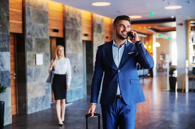 Homem sorridente de meia-idade vestido com roupa formal, caminhando no saguão de um hotel chique e falando ao telefone. ele está puxando sua mala.