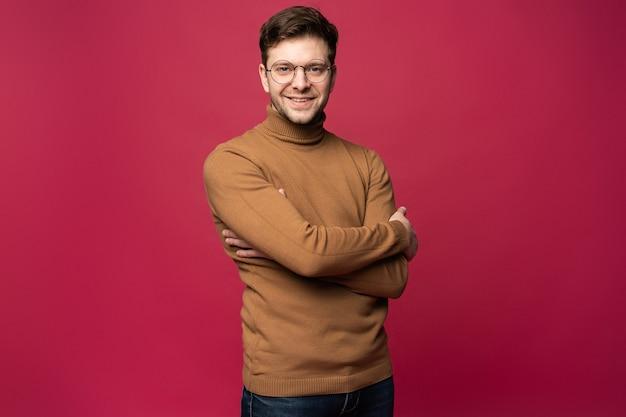 Homem sorridente de óculos e suéter em pé com os braços cruzados e olhando para longe. fundo rosa isolado.