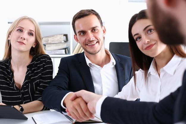 Homem sorridente de terno aperta as mãos para cumprimentá-lo no escritório
