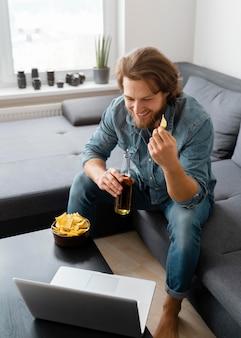 Homem sorridente de tiro completo com batatas fritas e bebida