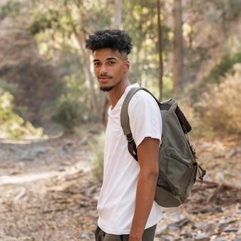 Homem sorridente de tiro médio carregando mochila