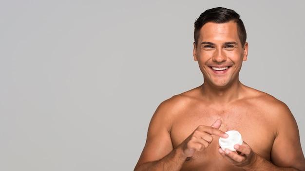 Homem sorridente de tiro médio com creme facial