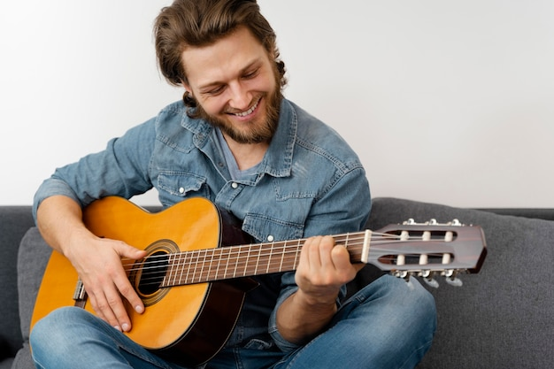 Homem sorridente de tiro médio com guitarra