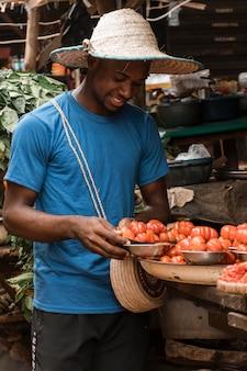Homem sorridente de tiro médio com legumes