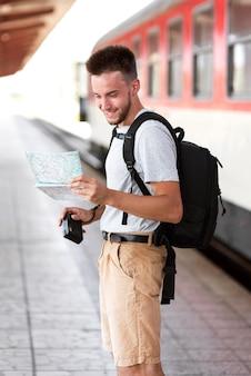Homem sorridente de tiro médio com mapa