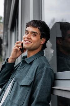 Homem sorridente de tiro médio falando ao telefone