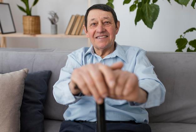 Homem sorridente de tiro médio no sofá