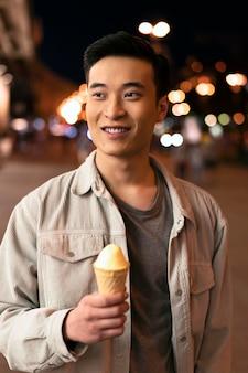 Homem sorridente de tiro médio segurando sorvete