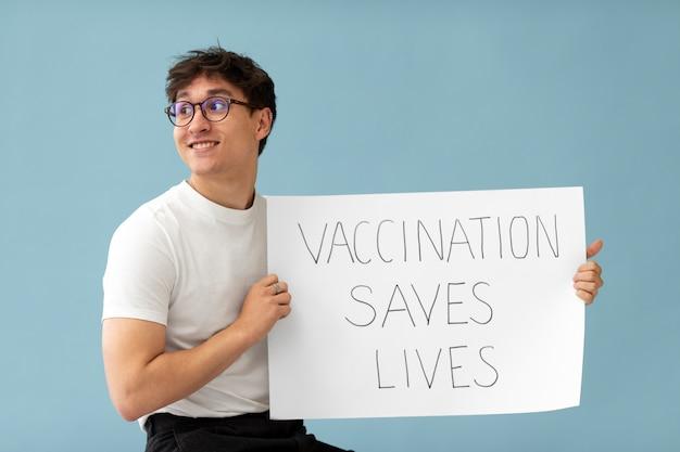 Homem sorridente de tiro médio segurando um cartaz
