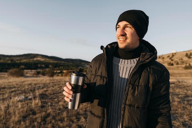 Homem sorridente de tiro médio segurando um frasco