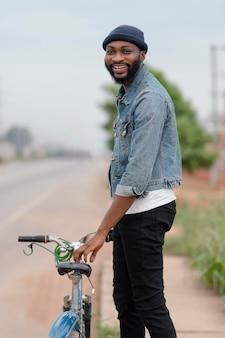 Homem sorridente de tiro médio segurando uma bicicleta