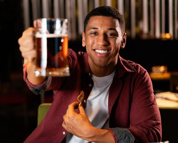 Homem sorridente de tiro médio segurando uma caneca de cerveja