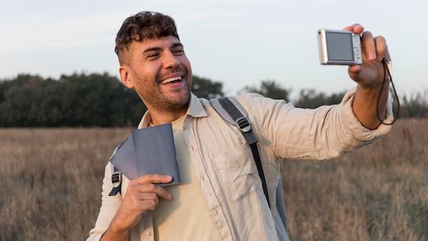 Homem sorridente de tiro médio tirando selfie
