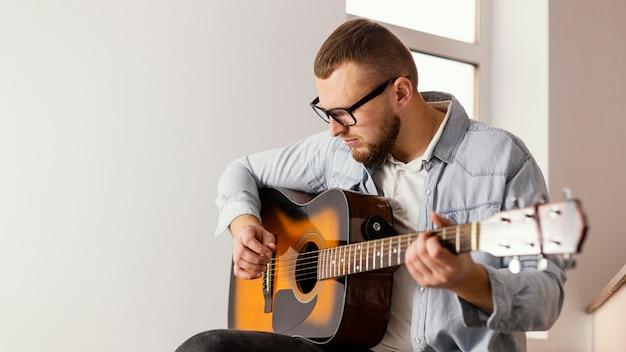 Homem sorridente de tiro médio tocando guitarra dentro de casa