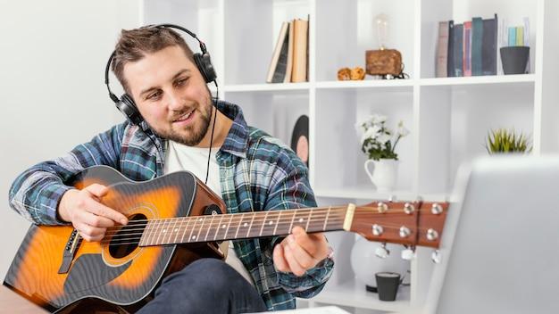Homem sorridente de tiro médio tocando guitarra