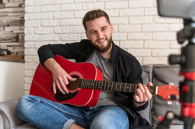 Homem sorridente de tiro médio tocando violão