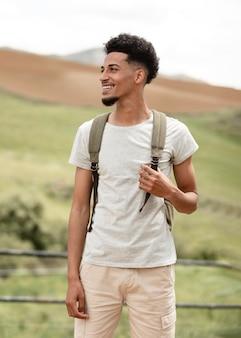 Homem sorridente de tiro médio usando mochila