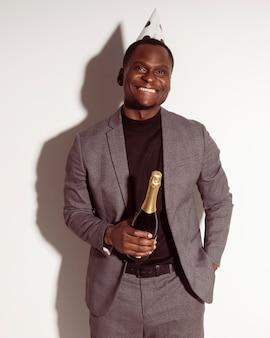 Homem sorridente de vista frontal segurando uma garrafa de champanhe