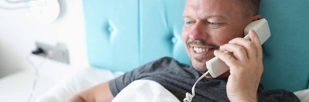 Homem sorridente deitado na cama falando ao telefone