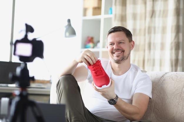 Homem sorridente demonstra tênis na câmera de vídeo
