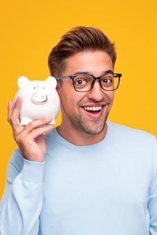 Homem sorridente demonstrando cofrinho branco