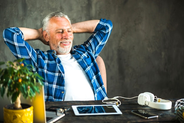 Homem sorridente descontraído na frente do laptop e tablet digital na mesa