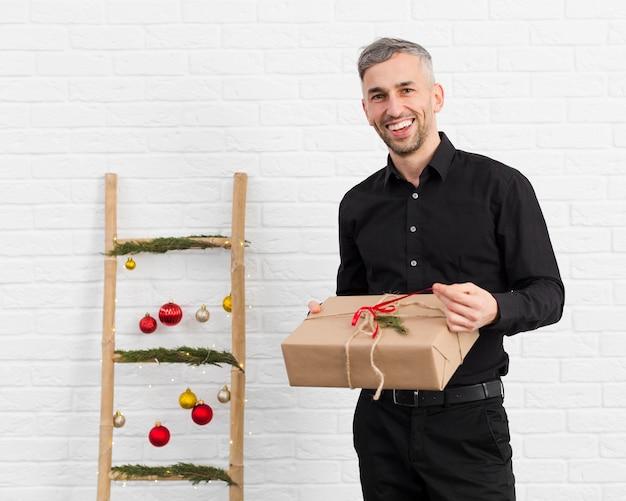 Homem sorridente desembrulhando um presente ao lado de uma escada com objetos de natal