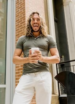 Homem sorridente, desfrutando de café ao ar livre