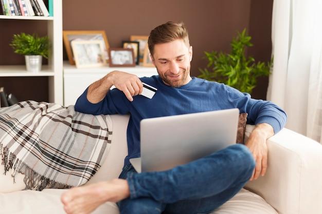 Homem sorridente durante compras online em casa