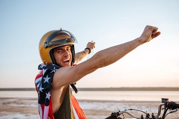 Homem sorridente e brutal com capacete dourado e capa da bandeira americana sentado em sua motocicleta com as mãos para cima