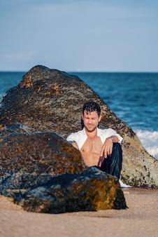 Homem sorridente e elegante na costa rochosa