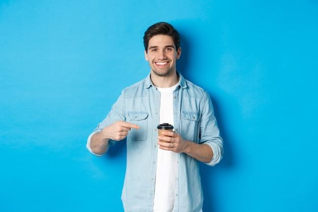 Homem sorridente e feliz apontando para um copo de papel com café, recomendando um café, em pé sobre um fundo azul