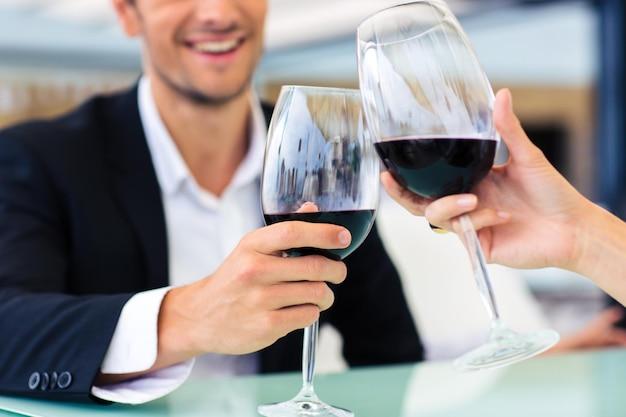 Homem sorridente e formal bebendo vinho tinto em restaurante