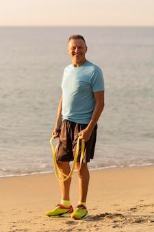 Homem sorridente e idoso com corda elástica na praia