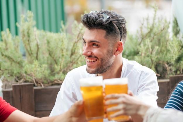 Homem sorridente e moderno que festeja com os amigos em um pub ao ar livre enquanto eles erguem os copos de cerveja gelada em um brinde com foco nas bebidas em seu rosto